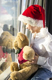 A boy in a red cap looks out the window. He is holding a teddy bear. Boy in white shirt Stock Photography