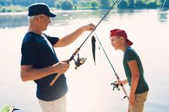 The old man and the boy are standing on the river bank with spinning arms. The old man shows the boy the fish he caught. A boy in a red cap and an old men in a stock photos