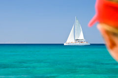 Boy in a red cap ;ooking on white catamaran Royalty Free Stock Photo