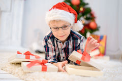 Boy in a red Christmas hat lying on the floor and opens his christmas gifts Stock Image