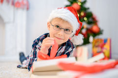 Boy in a red Christmas hat lying on the floor and opens his christmas gifts Royalty Free Stock Photos