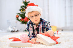 Boy in a red Christmas hat lying on the floor and opens his christmas gifts Stock Images