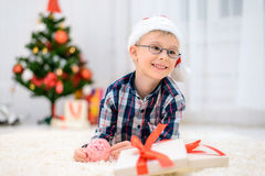 Boy in a red Christmas hat lying on the floor and opens his christmas gifts Royalty Free Stock Photography