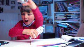 A boy at the school desk plays with fluorescent lights