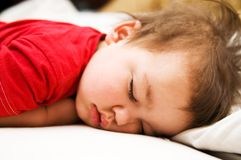 Boy in red dress sleeping on bed Stock Images