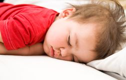 Boy in red dress sleeping on bed Royalty Free Stock Photo