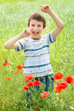 Boy in red flower meadow have fun Stock Photo