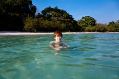 Boy with red hair is swimming in beautiful warm clear beach Stock Image