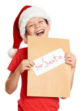 Boy in red hat with letter to santa - winter holiday christmas concept. Photo Stock Images