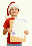 Boy in red hat with letter to santa - winter holiday christmas concept, yellow toned Royalty Free Stock Photography