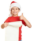 Boy in red hat with long scroll wishes to santa - winter holiday christmas concept Stock Images