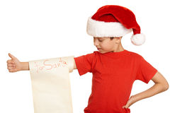 Boy in red hat with long scroll wishes to santa - winter holiday christmas concept Royalty Free Stock Photography