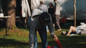 Boy in red hoody laying on a board on a cylinder, trying to balance it. With help of his dad or brother. Outdoor event in a park stock footage