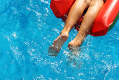 Boy in the red inflatable mattress in pool Royalty Free Stock Image