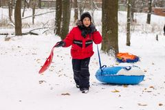A boy in a red jacket down on a sled with a snow slide stock photos