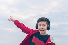 A boy in a red jacket and headphones smiling and shows his finger on the plane. Landing plane above sea waves in stormy weather. A boy in a red jacket and royalty free stock image