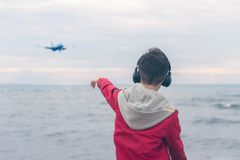 A boy in a red jacket and headphones smiling and shows his finger on the plane. Landing plane above sea waves in stormy weather. A boy in a red jacket and stock photos