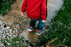 Boy in Red Jacket Jumping on Concrete Walkway Near Grass during Daytime Stock Photo