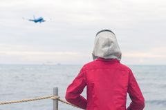 A boy in a red jacket looks at the sea waves in stormy rainy weather. Landing plane above sea waves in stormy rainy weather stock photo