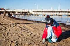 Boy in red jacket playing on beach Royalty Free Stock Images
