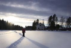 A person walking away in snow during a dramatic sunset with a dark sky and a house in finland royalty free stock photos