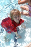 Boy in red in pool. Little boy too excited to go into the pool, forgot to take his shirt off Stock Photos