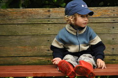 Boy in red rubber boots sitting on a rocking bench. Entangling Vines swing. Stock Image