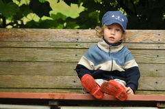 Boy in red rubber boots sitting on a rocking bench. Entangling Vines. Royalty Free Stock Images