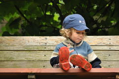 Boy in red rubber boots sitting on a rocking bench. Entangling Vines swing. Royalty Free Stock Photography