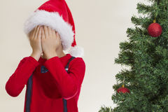 Boy in red Santa cap hidding his face with both hand near christmas tree Stock Photography
