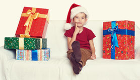 Boy in red santa helper hat with gift boxes - christmas holiday concept Stock Images