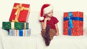 Boy in red santa helper hat with gift boxes - christmas holiday concept Royalty Free Stock Image
