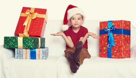 Boy in red santa helper hat with gift boxes - christmas holiday concept Stock Photos