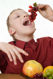 Boy in a red shirt eating grapes Stock Photo