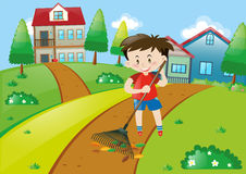 Boy in red shirt raking leaves at home Stock Photography