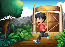 A boy with a red shirt running inside the fence Stock Image