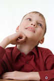 Boy in a red shirt sits and dreams Stock Photography