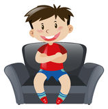 Boy in red shirt sitting on sofa Stock Image
