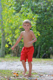 Boy in red shorts. Running on the beach Royalty Free Stock Image