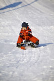 Boy in red on a sled  Royalty Free Stock Photo