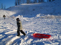 Boy with red sled in snow. Young boy pulling a red plastic sled over the snow stock photos