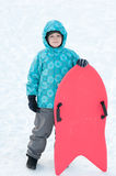 Boy with red sleds in winter Stock Photos