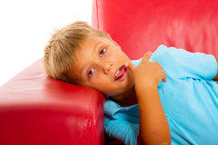 Boy on red sofa Stock Photos