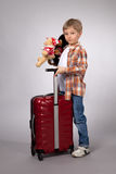 Boy with red suitcase with toys Royalty Free Stock Image