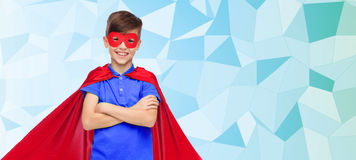 Boy in red super hero cape and mask. Carnival, childhood, power, gesture and people concept - happy boy in red super hero cape and mask over blue low poly Royalty Free Stock Photos