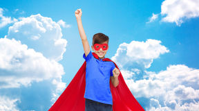 Boy in red super hero cape and mask showing fists Stock Photo