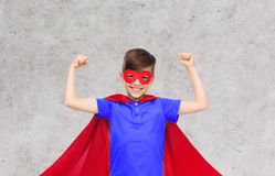 Boy in red super hero cape and mask showing fists Stock Photos