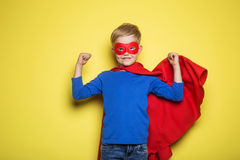 Boy in red super hero cape and mask. Superman. Studio portrait over yellow background Royalty Free Stock Image