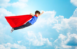 Boy in red superhero cape and mask flying over sky Royalty Free Stock Photo
