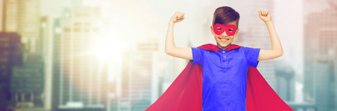 Boy in red superhero cape and mask showing fists Royalty Free Stock Image